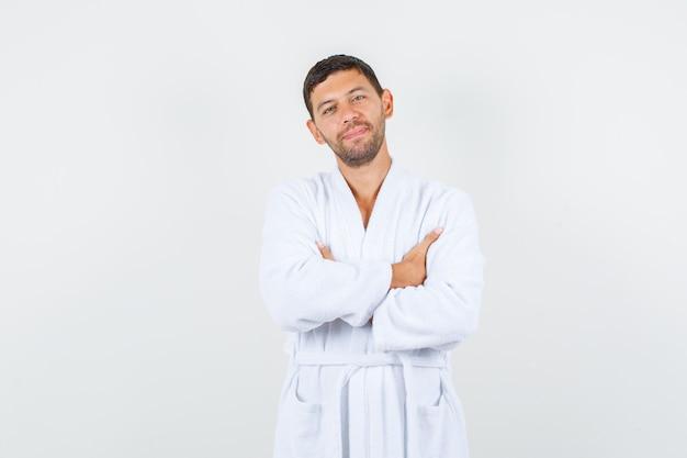 Junger mann, der mit verschränkten armen im weißen bademantel steht und froh schaut, vorderansicht.