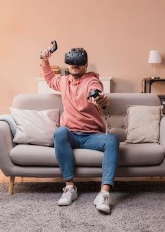 Junger mann, der mit virtuellem kopfhörer spielt