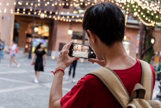 Junger mann, der mobilen smartphone verwendet, machen ein foto durch kamera-app.