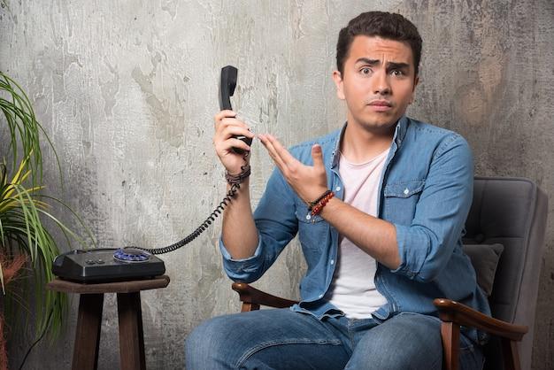 Junger mann, der mobilteil hält und auf stuhl sitzt. hochwertiges foto