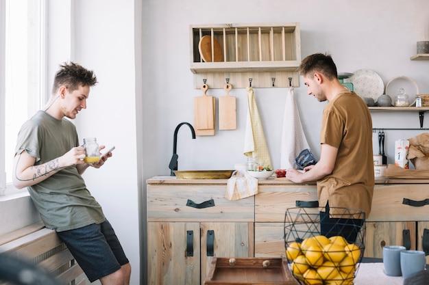 Junger mann, der mobiltelefon während sein freund zubereitet lebensmittel in der küche verwendet