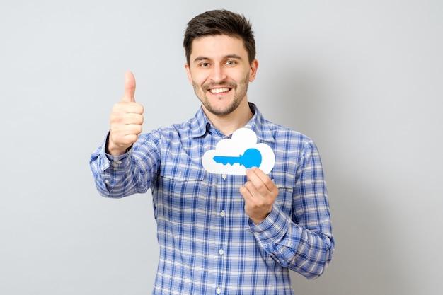 Junger mann, der modell der wolke mit blauem schlüssel hält