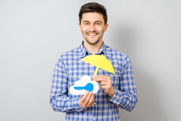 Junger mann, der modell der wolke mit blauem schlüssel und gelbem regenschirm hält