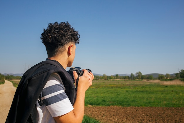 Junger mann, der moderne digitalkamera anhält