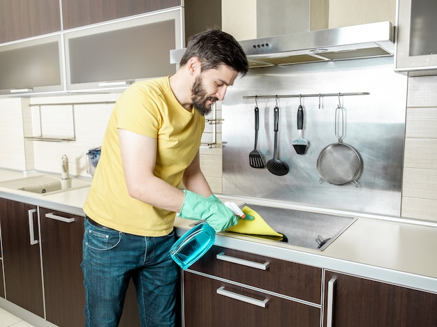 Junger mann, der moderne küche reinigt