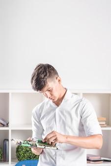 Junger mann, der modernes pc-computermotherboard mit ram-verbindungsstückschlitz hält