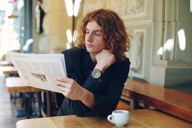 Junger mann, der morgens zeitung liest