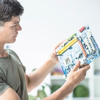 Junger mann, der motherboardstromkreis betrachtet