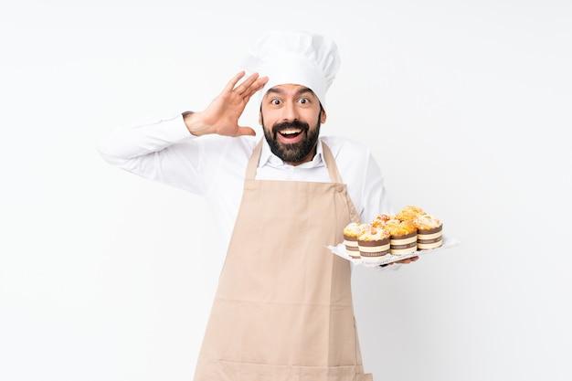 Junger mann, der muffinkuchen mit überraschungsausdruck hält