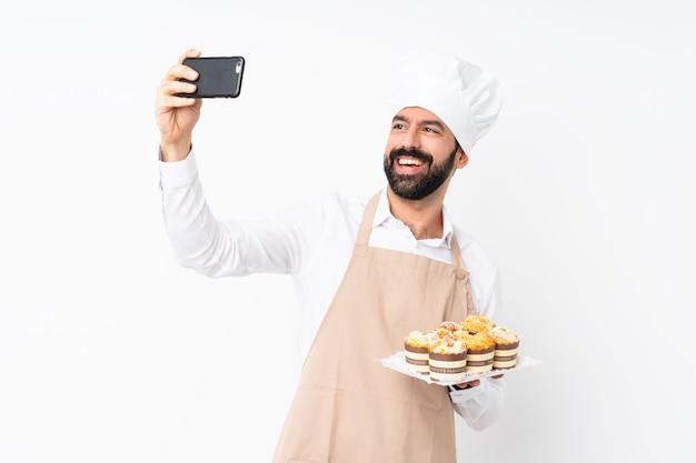 Junger mann, der muffinkuchen über dem lokalisierten weiß macht ein selfie hält