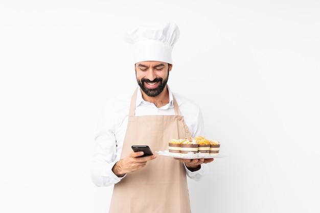 Junger mann, der muffinkuchen über dem lokalisierten weiß sendet eine mitteilung mit dem mobile hält