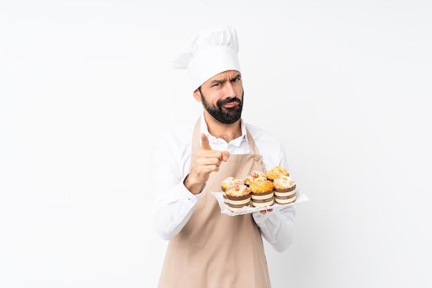 Junger mann, der muffinkuchen über lokalisiertem weiß frustriert hält und auf die front zeigt