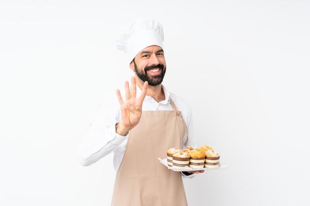 Junger mann, der muffinkuchen über lokalisiertem weiß glücklich hält und vier mit den fingern zählt