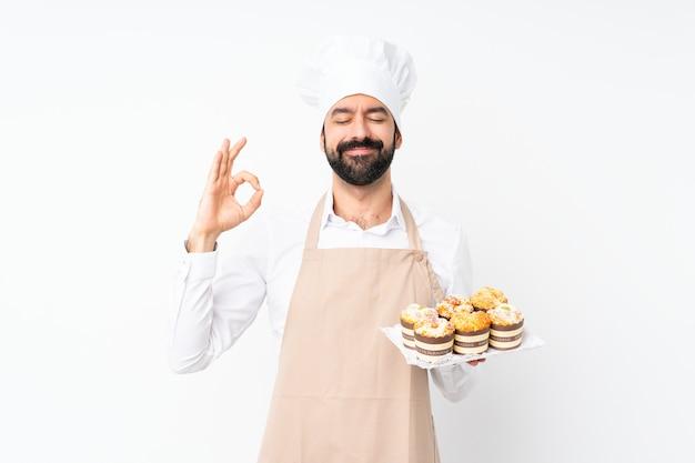 Junger mann, der muffinkuchen über lokalisiertem weiß in der zenhaltung hält