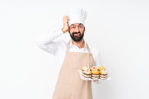 Junger mann, der muffinkuchen über lokalisiertem weiß mit einem ausdruck der frustration und des nichtverständnisses hält