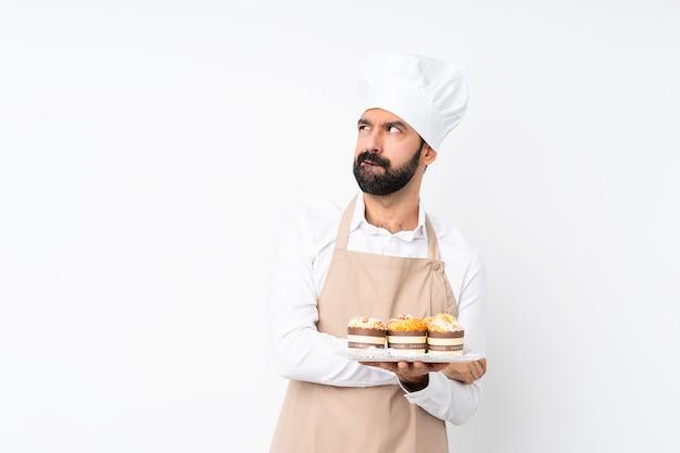 Junger mann, der muffinkuchen über lokalisiertem weiß mit verwirren gesichtsausdruck hält