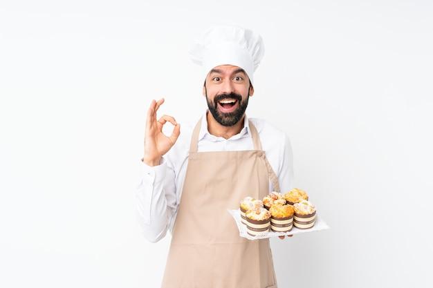 Junger mann, der muffinkuchen über lokalisiertem weiß überrascht hält und okayzeichen zeigt