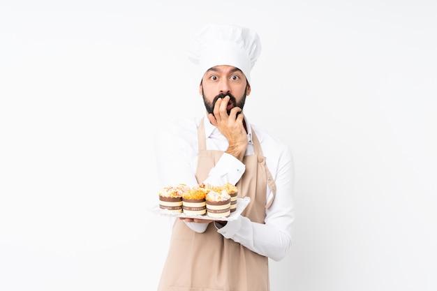 Junger mann, der muffinkuchen über lokalisiertem weiß überrascht und beim schauen recht entsetzt hält