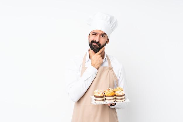 Junger mann, der muffinkuchen über lokalisiertem weißem denken hält