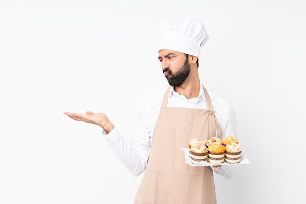 Junger mann, der muffinkuchen über lokalisiertem weißem haltenem copyspace mit zweifeln hält