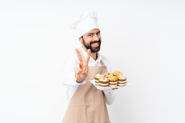 Junger mann, der muffinkuchen über lokalisiertem weißem lächeln hält und siegeszeichen zeigt