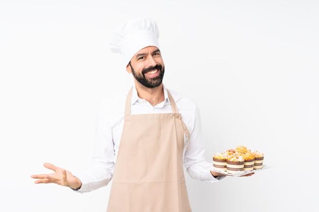 Junger mann, der muffinkuchen über lokalisiertem weißem lächeln hält