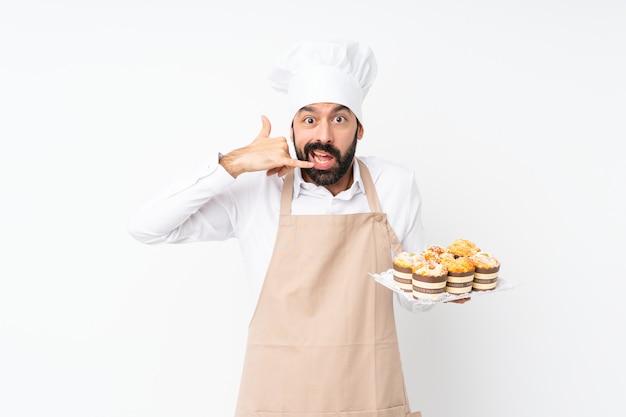 Junger mann, der muffinkuchen über lokalisierter weißer herstellungstelefongeste und -c $ zweifeln hält