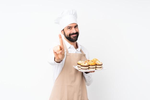 Junger mann, der muffinkuchen über lokalisierter weißer vertretung hält und einen finger anhebt