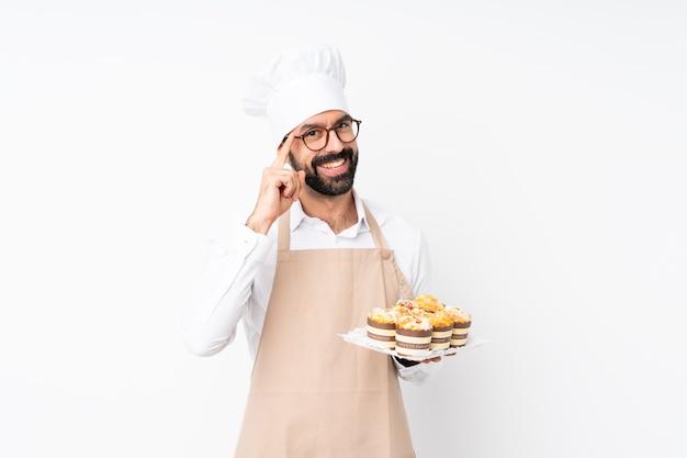 Junger mann, der muffinkuchen über lokalisierter weißer wand mit gläsern und glücklich hält