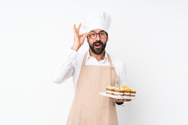 Junger mann, der muffinkuchen über lokalisierter weißer wand mit gläsern und überrascht hält