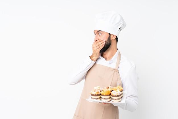Junger mann, der muffinkuchenbedeckungsmund hält und zur seite schaut