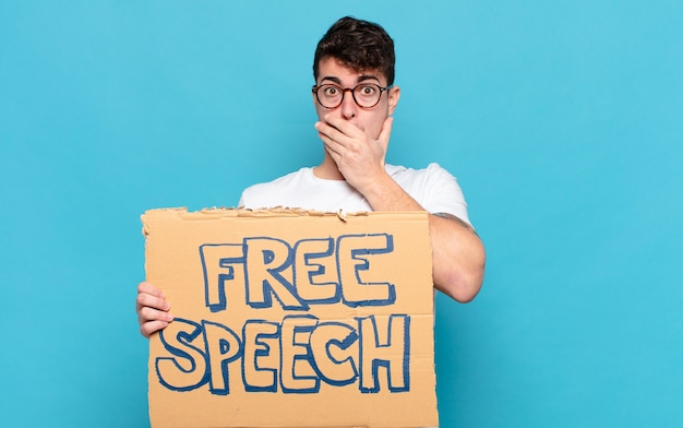 Junger mann, der mund mit den händen mit einem schockierten, überraschten ausdruck bedeckt, ein geheimnis hält oder oops sagt