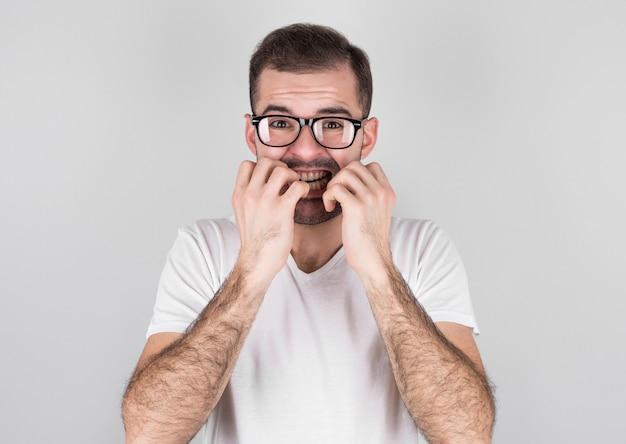 Junger mann, der mund mit händen und runden augen bedeckt, runde brille trägt, tiefes erstaunen und angst erfährt, isoliert auf grauer wand
