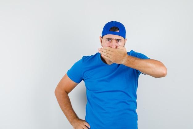 Junger mann, der mund mit hand im blauen t-shirt und in der kappe bedeckt und ernst schaut