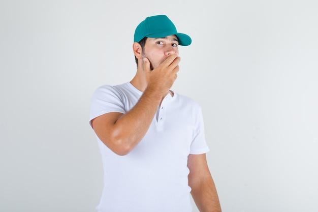 Junger mann, der mund mit hand im weißen t-shirt mit kappe bedeckt und schockiert schaut