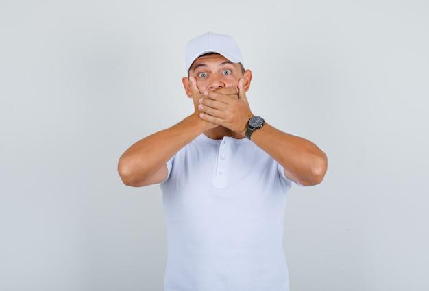 Junger mann, der mund mit seinen händen im weißen t-shirt, mütze bedeckt und schockiert, vorderansicht schaut.