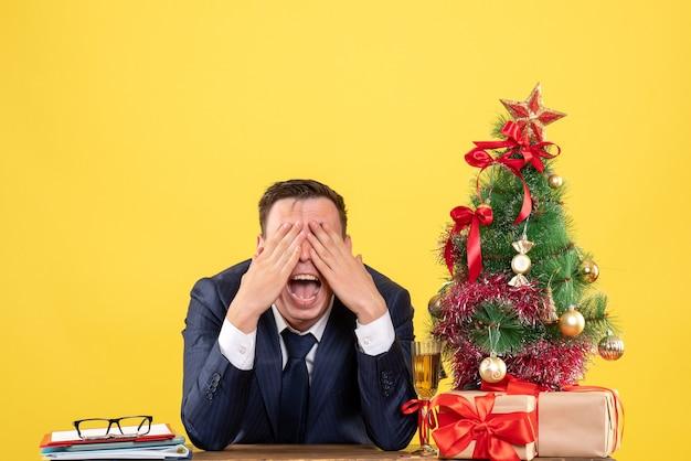 Junger mann, der mund öffnet, der augen mit den händen bedeckt, die am tisch nahe weihnachtsbaum sitzen und auf gelb präsentieren