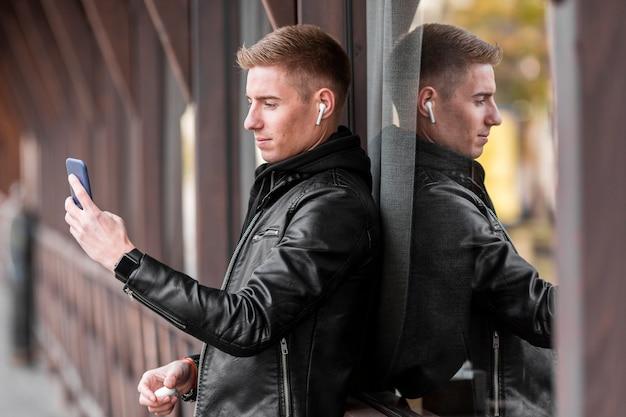 Junger mann, der musik auf kopfhörern beim machen eines fotos hört