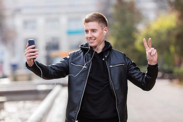 Junger mann, der musik auf kopfhörern beim nehmen eines selfie hört