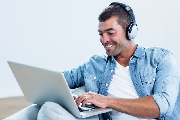 Junger mann, der musik bei der anwendung des laptops hört