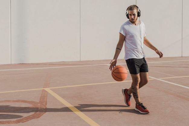 Junger mann, der musik beim basketball vor gericht spielen hört