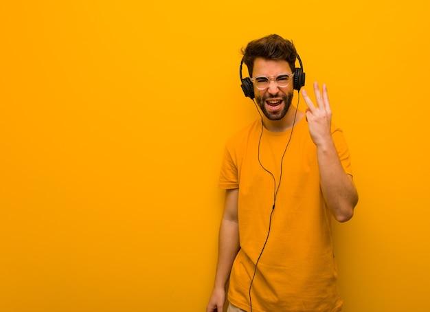 Junger mann, der musik hört, die nummer drei zeigt