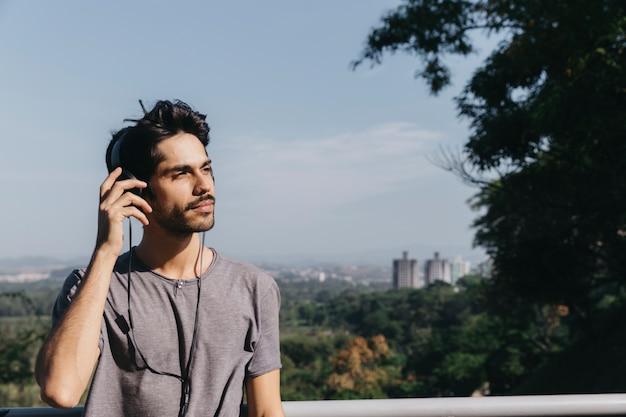 Junger mann, der musik im park genießt