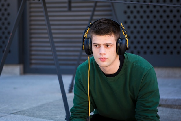 Junger mann, der musik in den kopfhörern hört