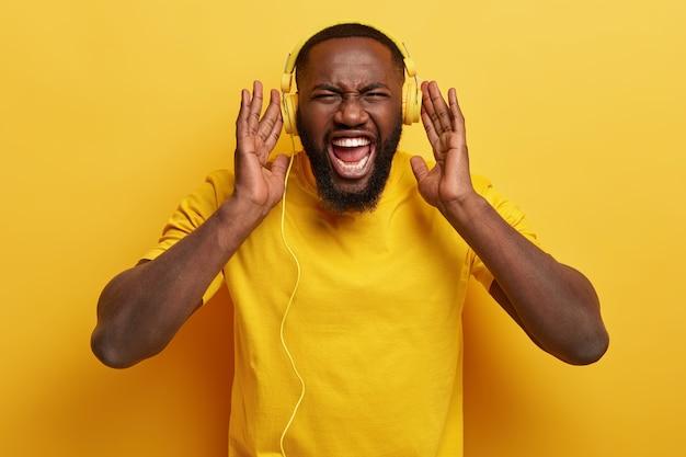 Junger mann, der musik in kopfhörern hört