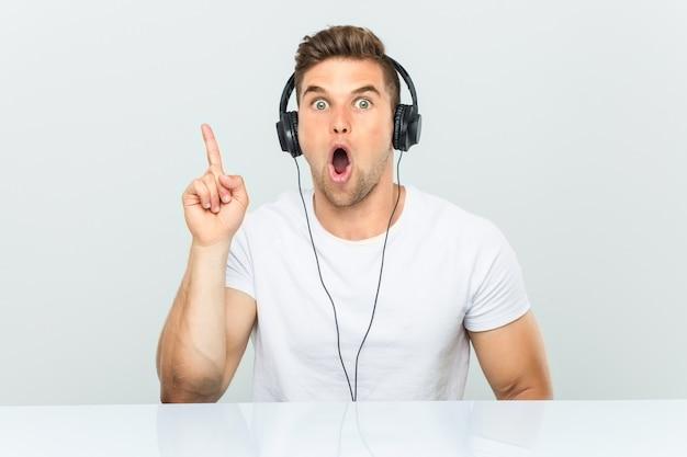 Junger mann, der musik mit den kopfhörern haben etwas großartige idee hört