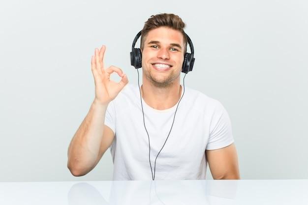 Junger mann, der musik mit den kopfhörern nett und überzeugt hört, okaygeste zeigend.