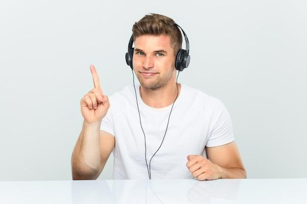 Junger mann, der musik mit den kopfhörern zeigen nummer eins mit dem finger hört.