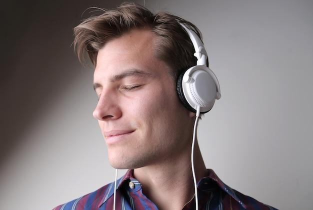 Junger mann, der musik mit kopfhörern gegen eine graue wand hört