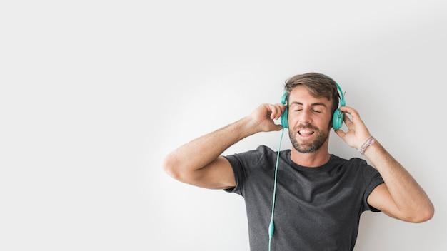 Junger mann, der musik mit kopfhörern genießt